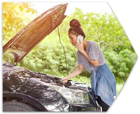 A woman on the phone checking the engine of her broken down car